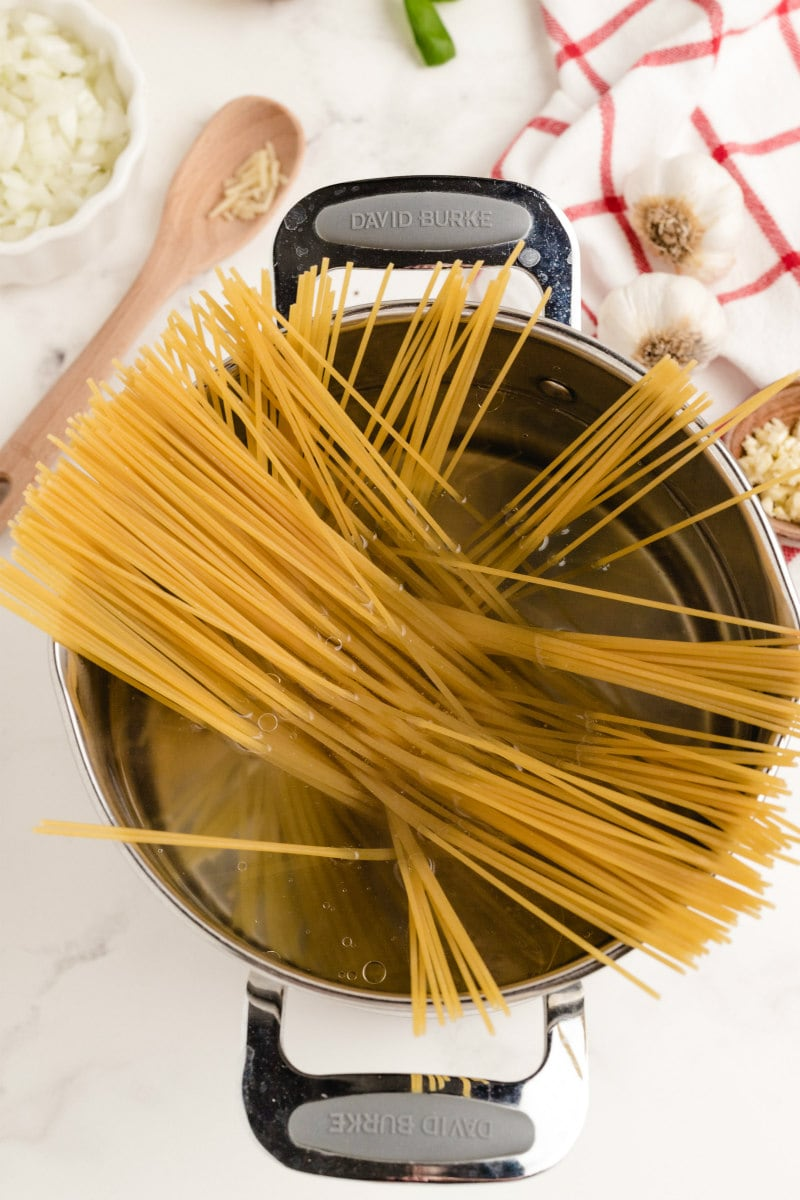 adding pasta to water in a pot