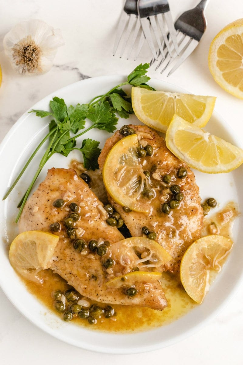 chicken piccata on a white plate with lemon and parsley
