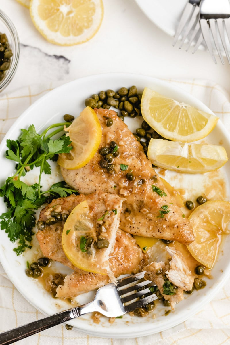 chicken piccata on a white plate with fork