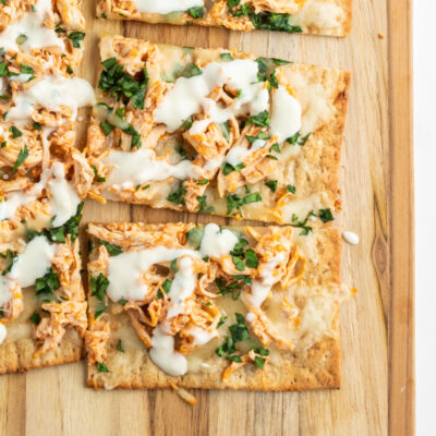 sliced buffalo chicken flatbread on cutting board