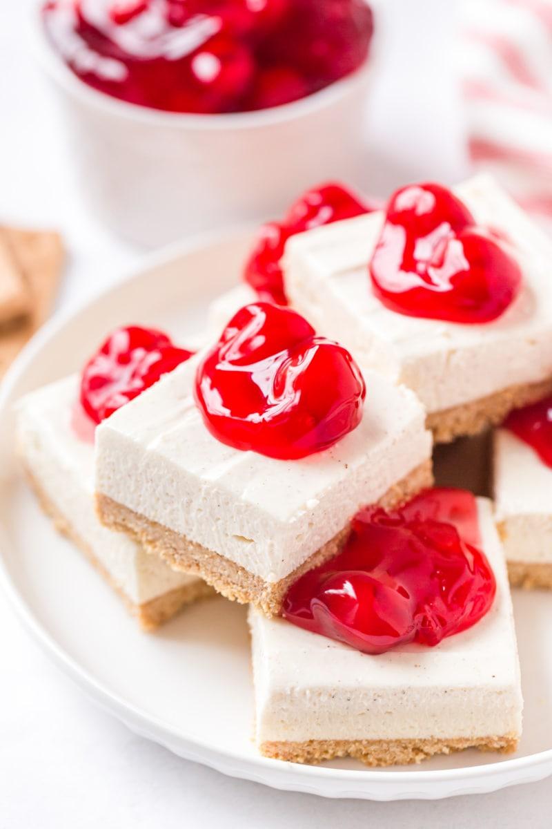 cherry cheesecake bars stacked on platter