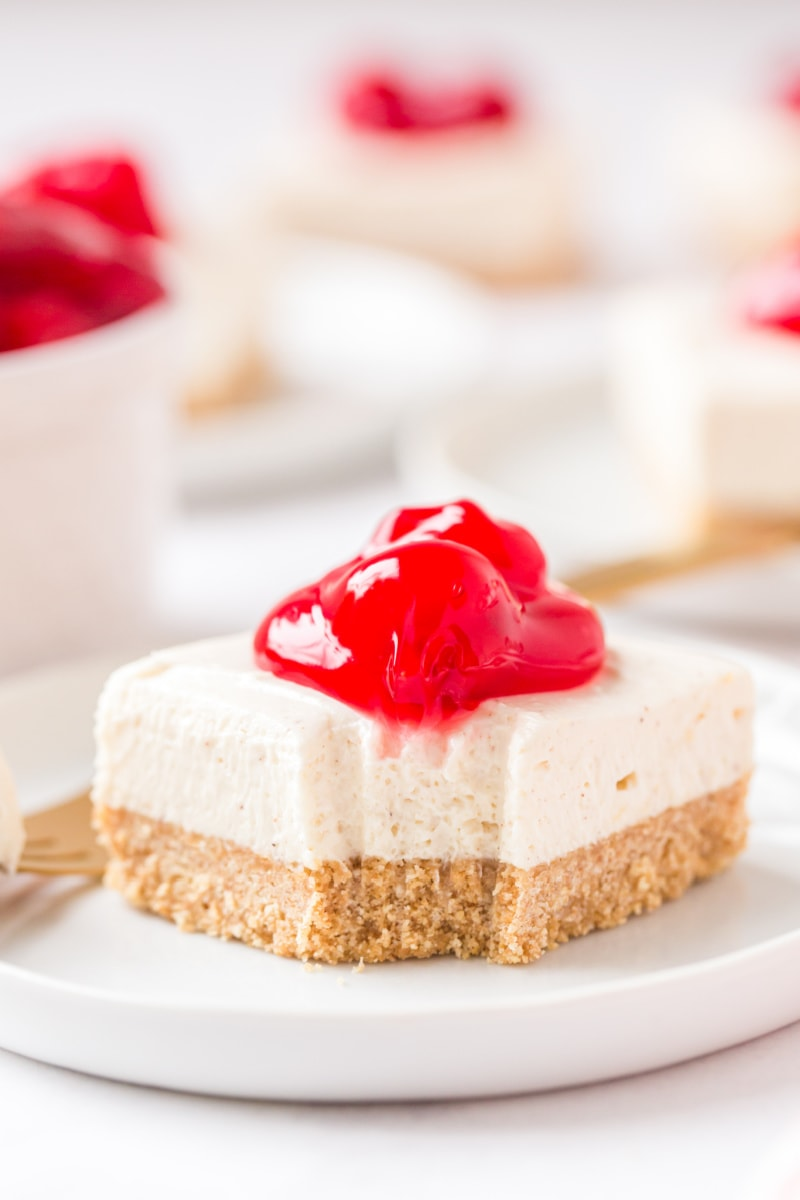 cherry cheesecake bar on white plate with bite out of it