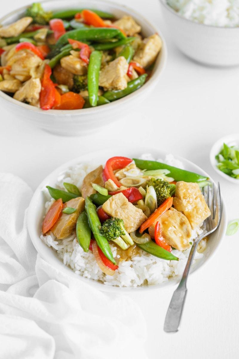 teriyaki chicken stir fry served over rice on white plates