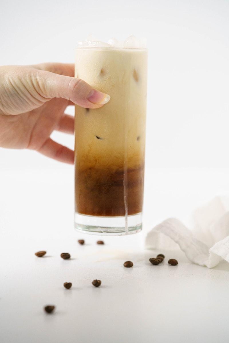 hand holding iced vanilla latte