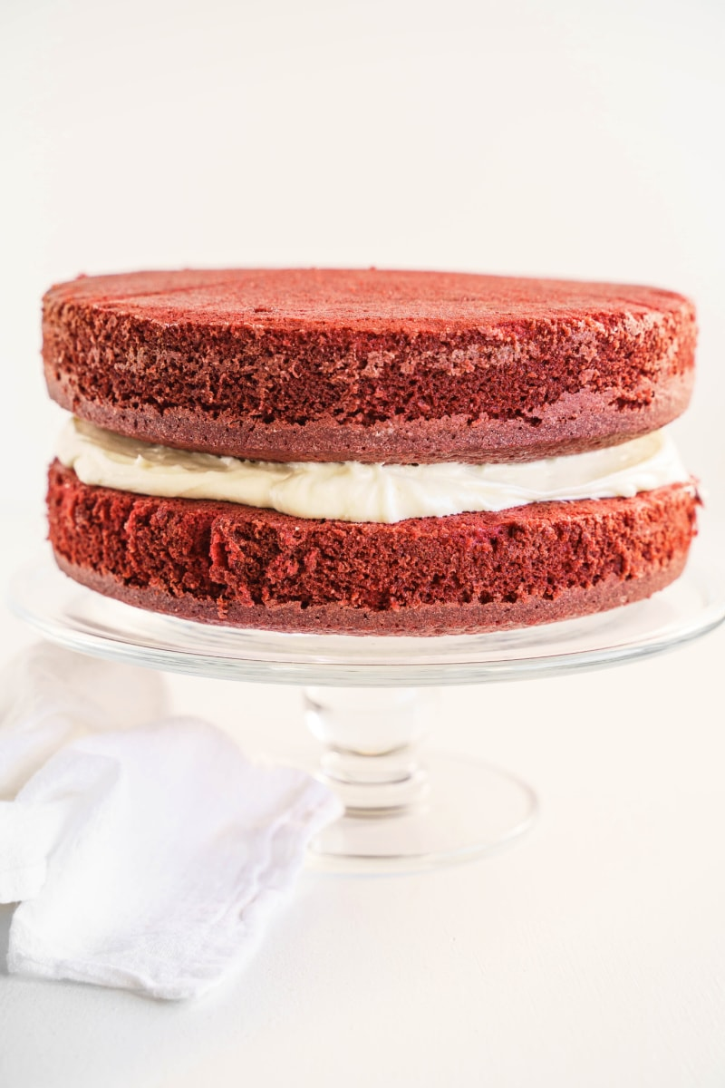 two layers of red velvet cake on cake platter with white frosting in between