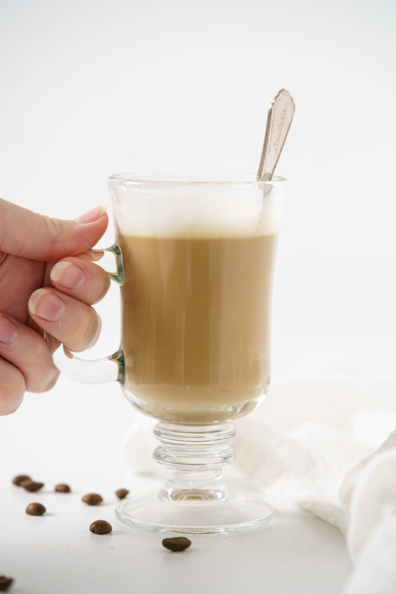hand holding a cup of vanilla latte