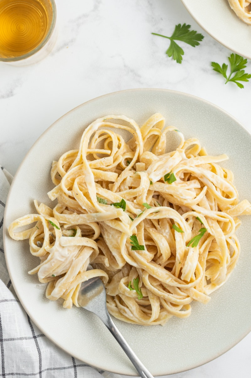 serving of fettuccine alfredo on white plate with fork