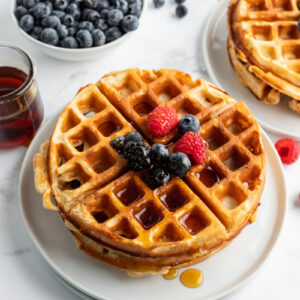 stack of waffles on plate topped with fruit and syrup