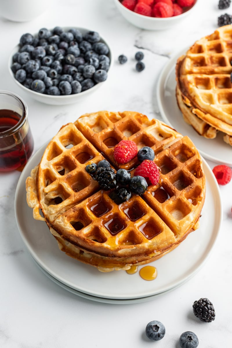 stack of waffles on a plate garnished with fruit and syrup