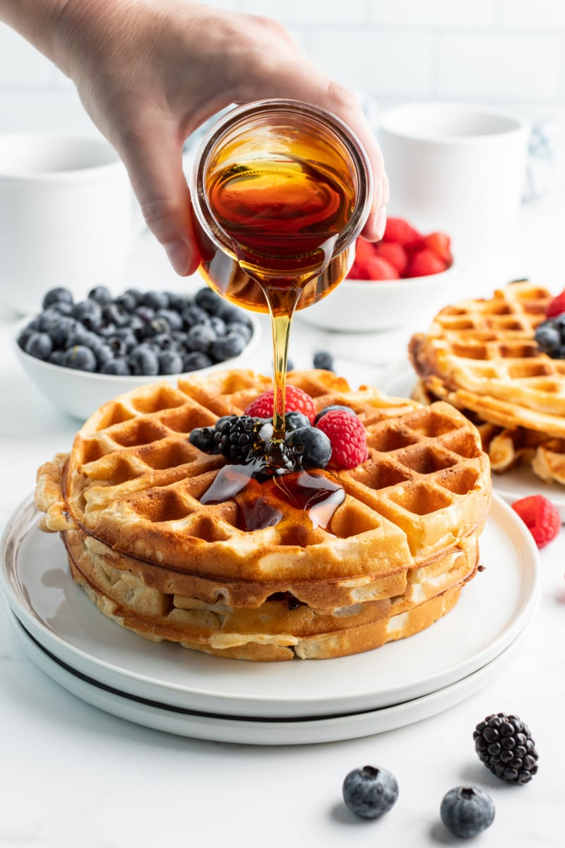 pour syrup on a stack of Greek yogurt waffles with fruit on top