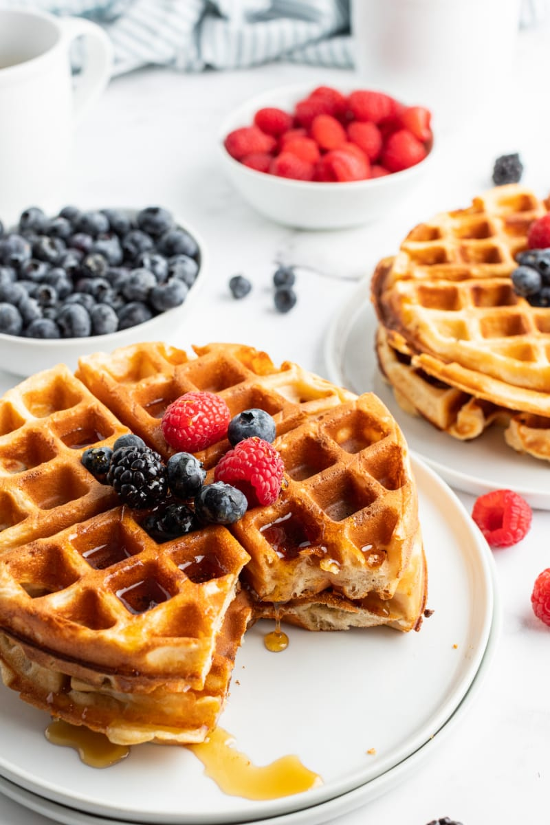 stack of waffles on a plate with a cut out piece topped with fruit