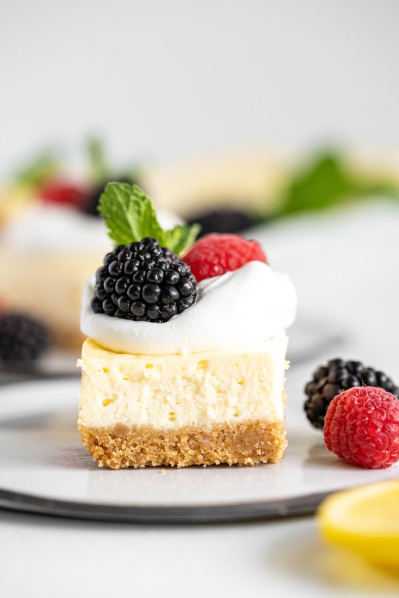 lemon cheesecake bar topped with whipped cream and berries