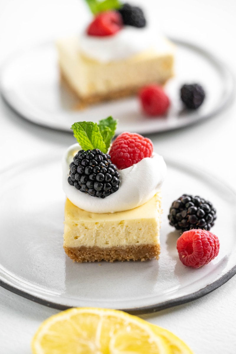 Lemon cheesecake bar on white plate topped with whipped cream and berries