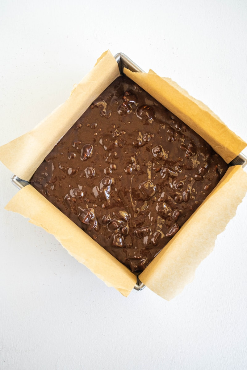 brownie batter in square pan ready for oven