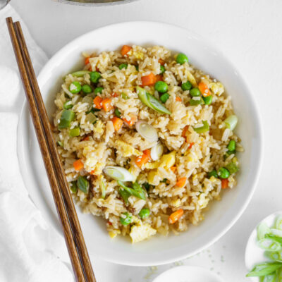 vegetable fried rice in a white bowl with chopsticks