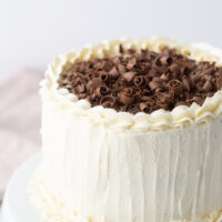 wedding cake with white frosting and chocolate shavings on top