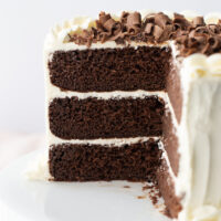 chocolate wedding cake with white frosting and chocolate shavings on top cut into to see inside