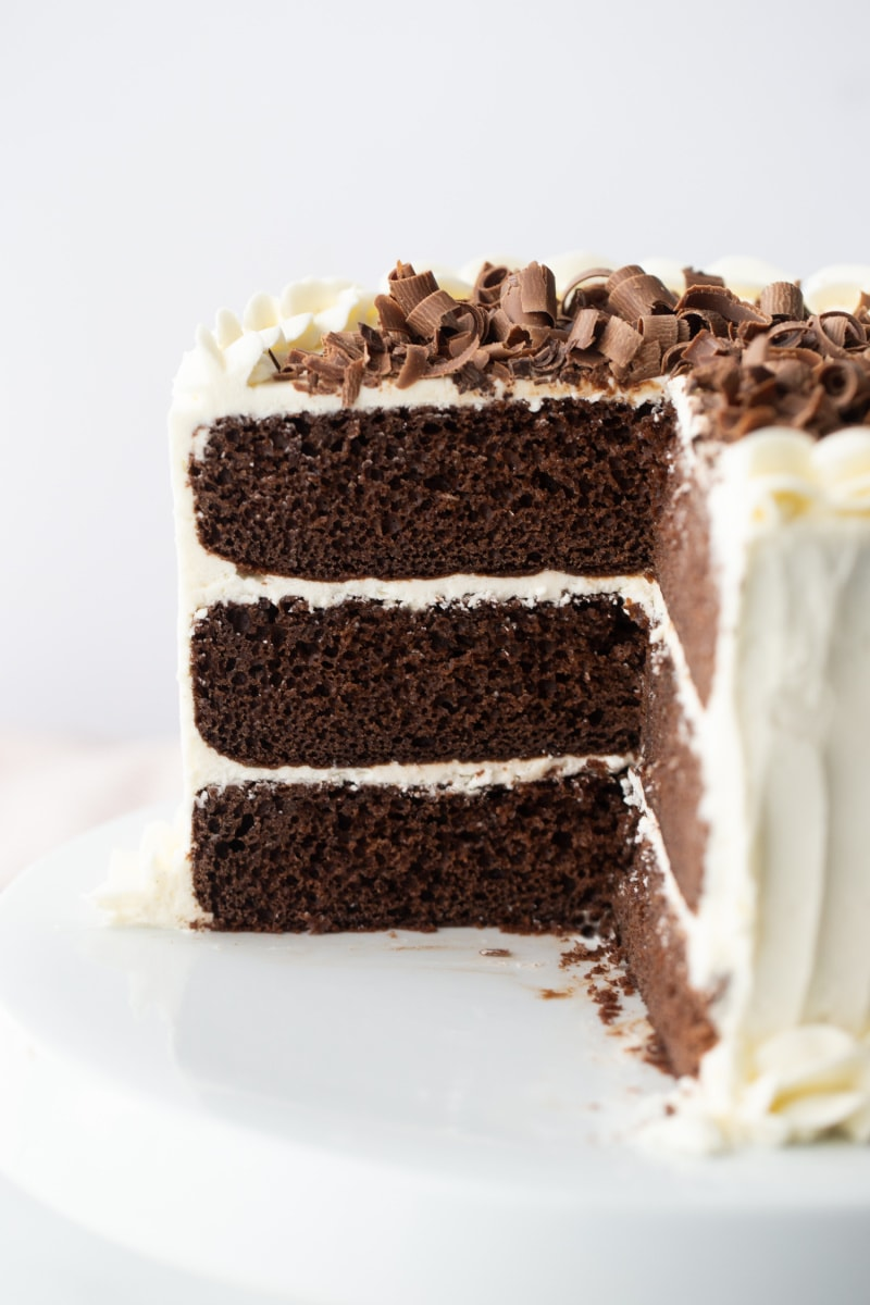 chocolate wedding cake with white frosting and chocolate shavings on top cut to see inside
