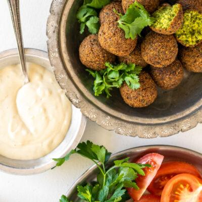 falafel in bowl and tahini sauce and fresh veggies