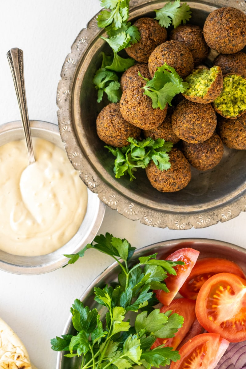 falafel in a bowl with tahini sauce and fresh vegetables