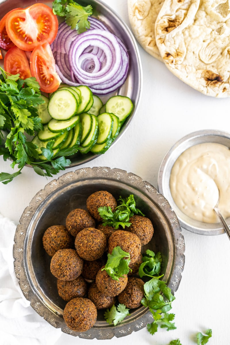 falafel in a bowl with bowl of tahini sauce and fresh vegetables and flatbread