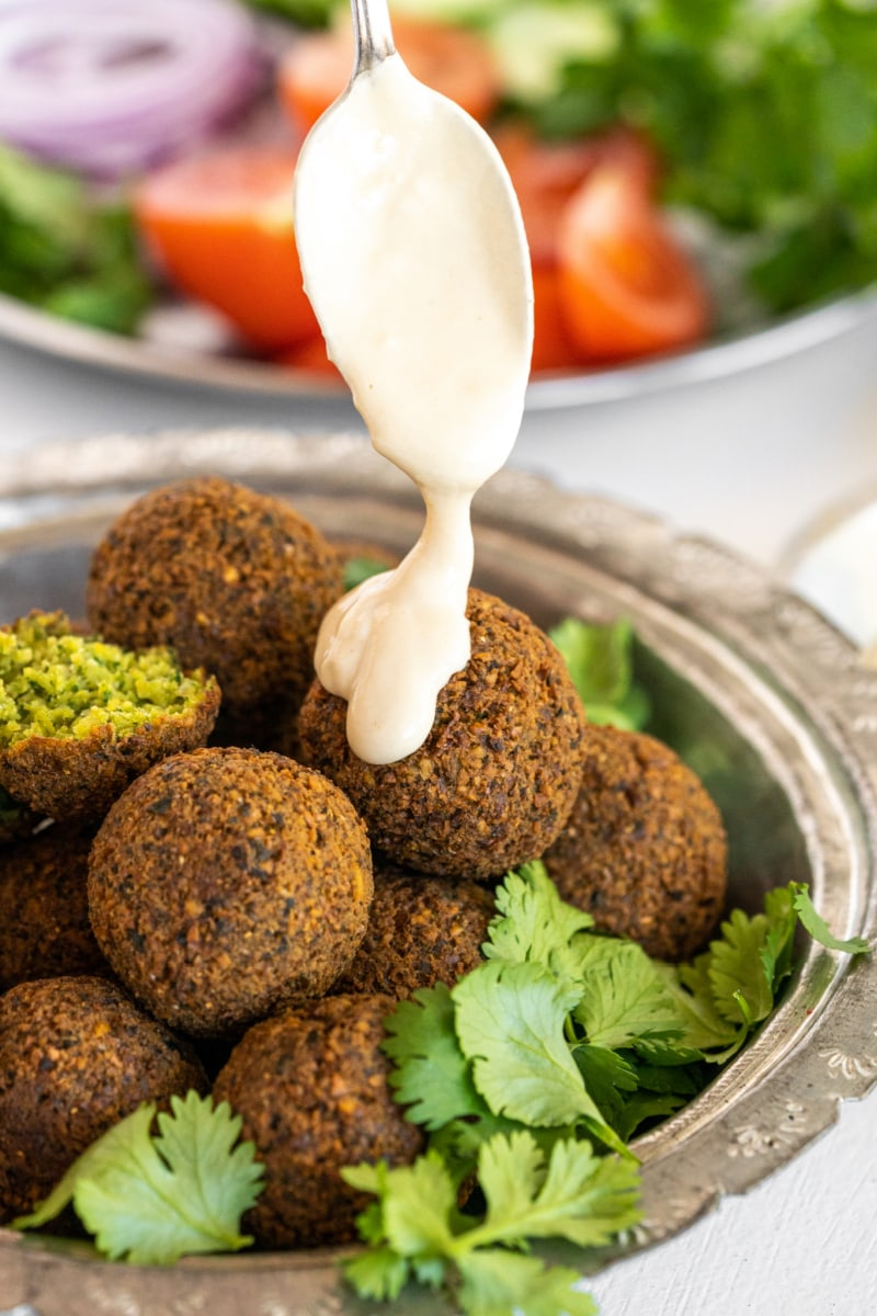 tahini sauce drizzled over falafel in a bowl