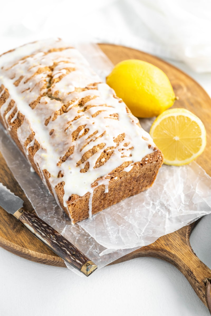 loaf of iced lemon zucchini bread on cutting board with lemons