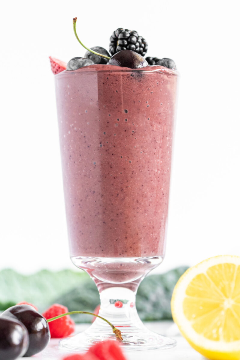 berry detox smoothie in a tall glass with fresh fruit garnishes