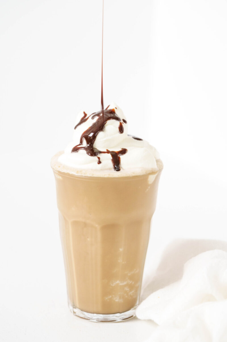 pouring chocolate syrup on mocha frappuccino