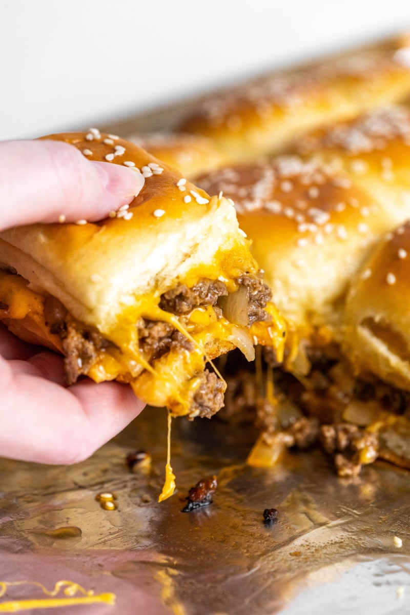hand pulling a cheeseburger slider out of a pan