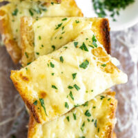 slices of cheesy garlic bread stacked on plate