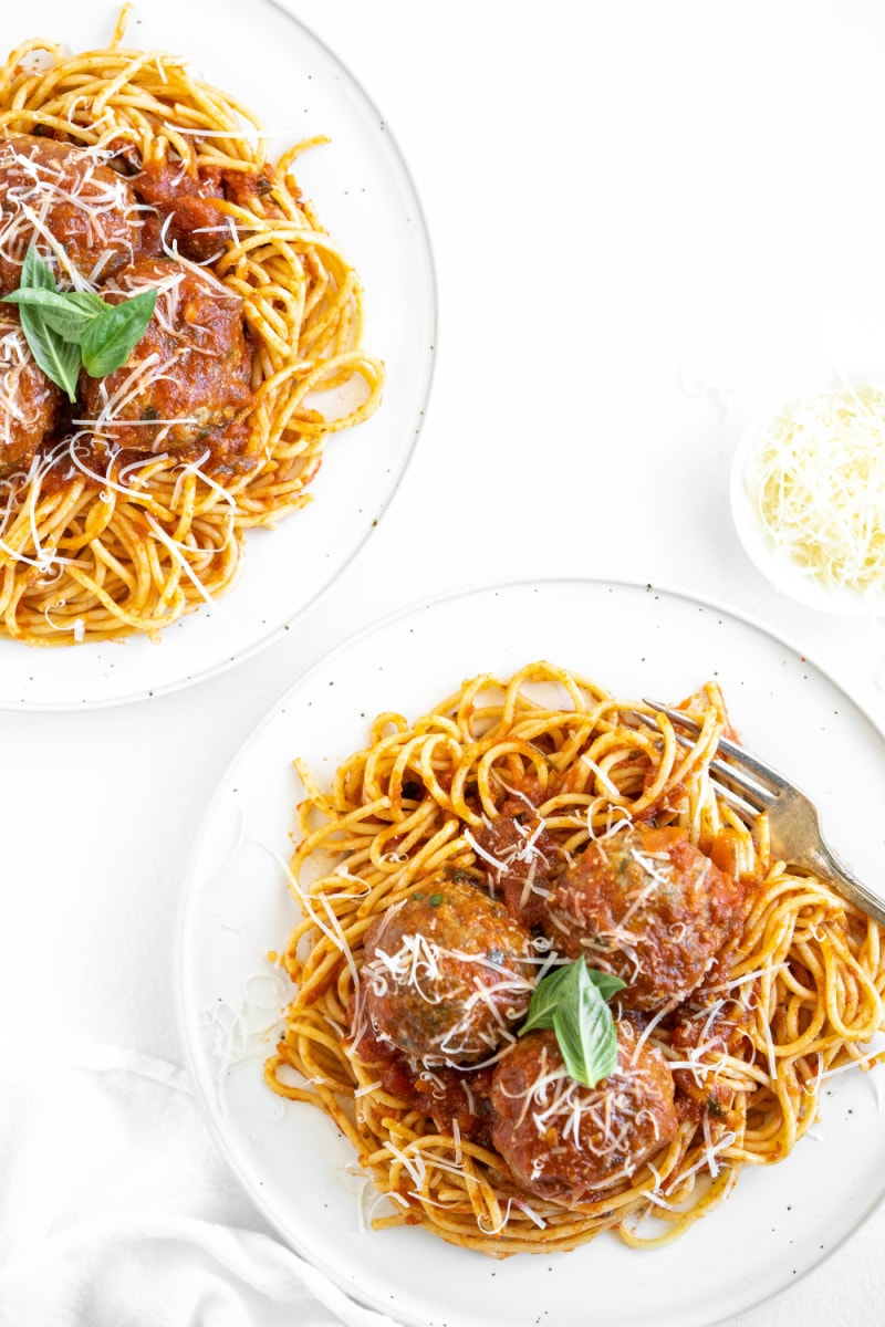 spaghetti and meatballs on two white plates