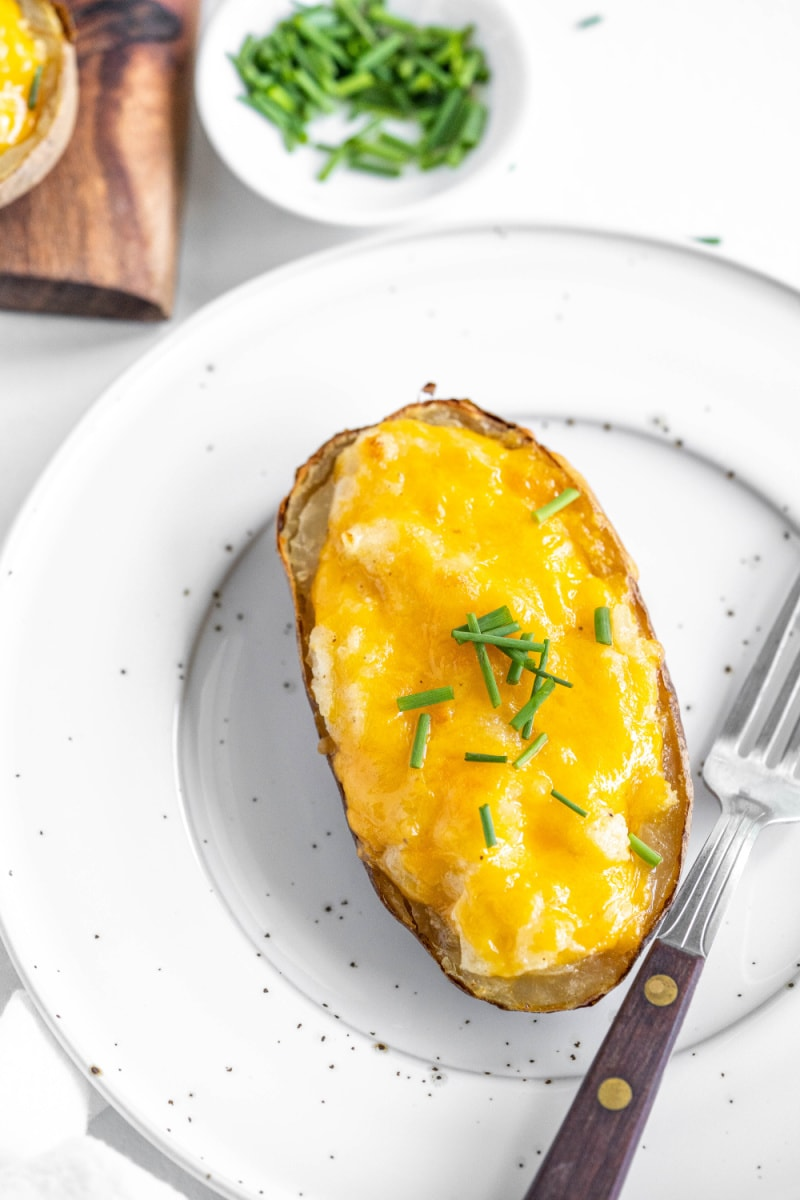 one serving of twice baked potato on white plate